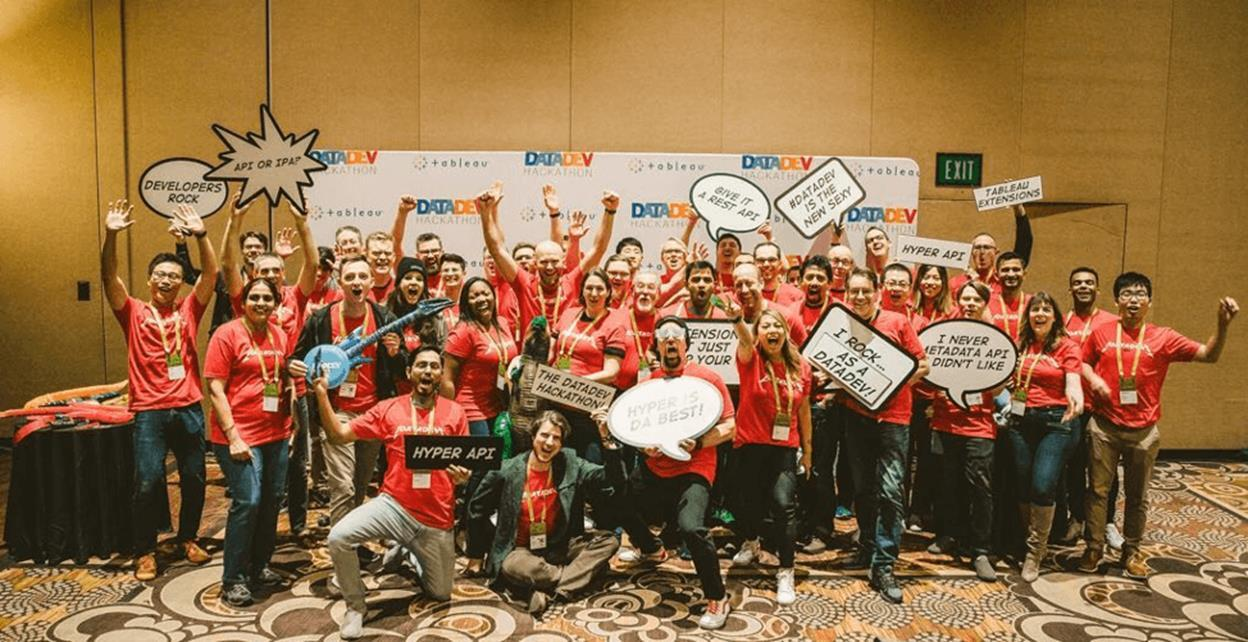 Large group cheering and smiling, all wearing red TC t-shirts and holding fun data and dev-themed signs, posing in a conference room