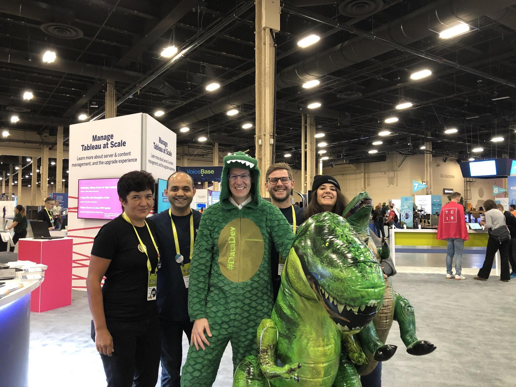 Group of four posing with man in glasses in T-Rex costume, alongside a giant inflatable T-Rex