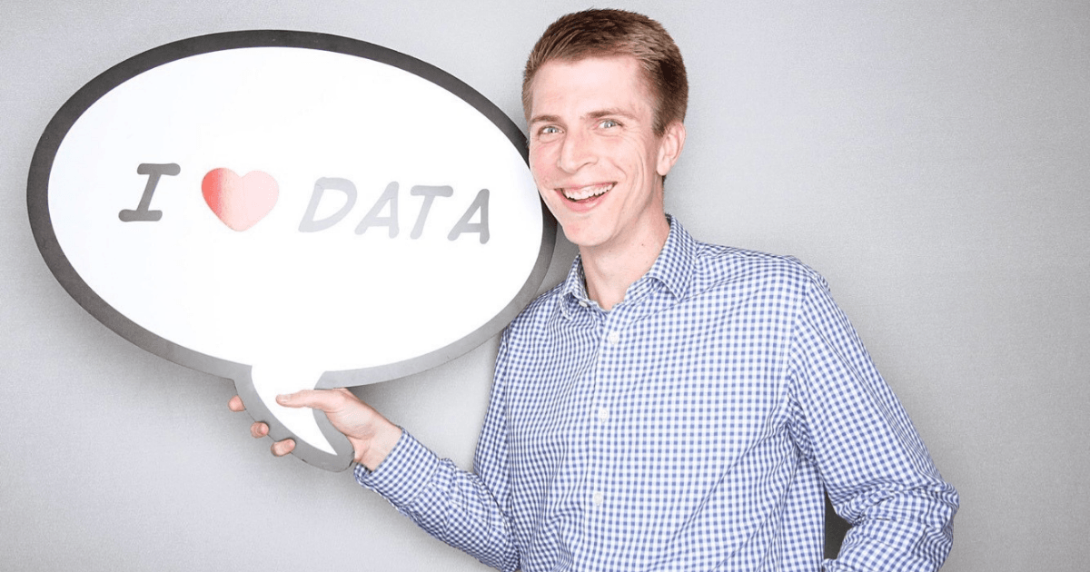 """Smiling man in button-down shirt holding an """"I <3 data"""" sign"""